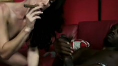 Sexy slender brunette with small tits smokes a cigar and blows a huge black cock