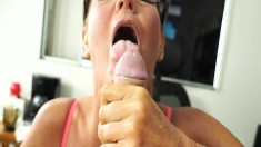 Skinny cougar in glasses kneels to stroke a cock with her fingers and mouth