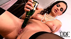 Brunette babe Eve has a glass of champagne and shoves the bottle up her twat