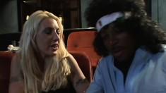 Insatiable blonde sucks and fucks a huge black dick in a movie theatre